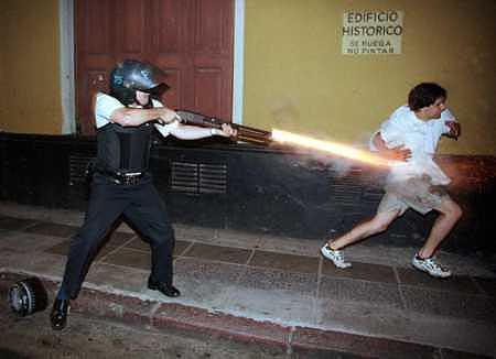 Un policía dispara balas de goma contra un manifestante, la madrugada del viernes en Buenos Aires. La tensión social crció luego que el gobierno pusiera en marcha la devaluación de la moneda y mantuviera secuestrados los depósitos en los bancos. El manifestante fue herido en su abdomen. Foto Reuters