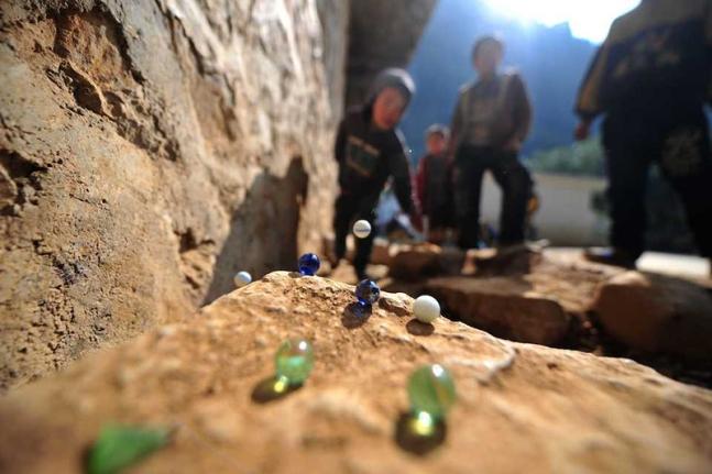 (131228) -- GUANGXI, diciembre 28, 2013 (Xinhua) -- Imagen del 19 de diciembre de 2013 de un grupo de niÒos jugando canicas en la Escuela Primaria Nonglei en el municipio de Bansheng en el condado autÛnomo Yao de Dahua, de la RegiÛn AutÛnoma Zhuang de Guangxi, al sur de China. (Xinhua/Huang Xiaobang) (jg) (rt)